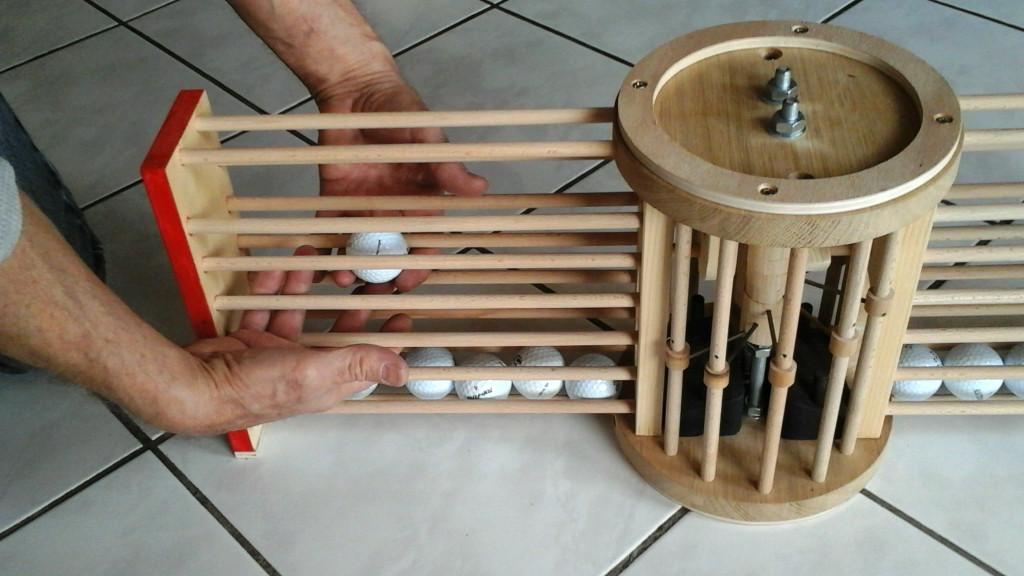 Avec les doigts des deux mains on fait monter les boules jusqu'en haut, puis on les glisse dans la tour centrale