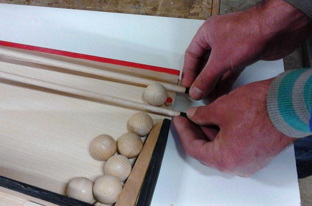 Moyen de saisir la boule : les baguettes de guidage passent dessous la boule et se resserrent afin de la faire monter dessus.